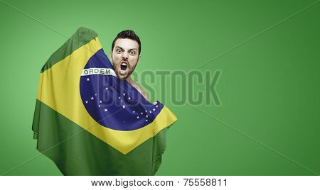 Brazilian fan holding the flag of Brazil celebrates on green background