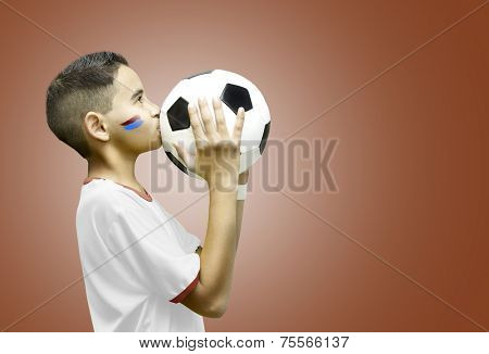 American little boy kissing a soccer ball on red background