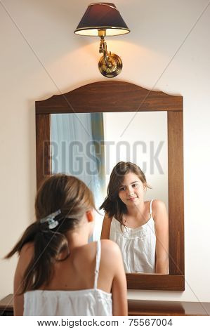 A beautiful teen girl studies her appearance as she looks into the mirror at her
