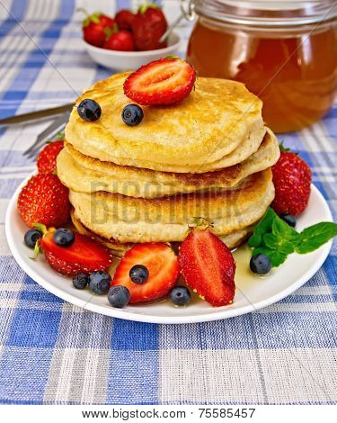 Flapjacks with strawberries and blueberries on blue tablecloth