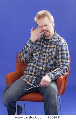 Tired Man Sitting On A Chair