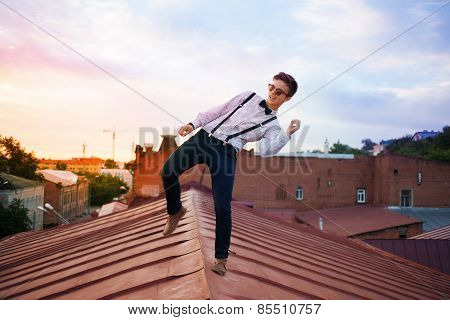 Young Bold Girl Woman Hipster Jumping On The Roof, Dressed Like A Boy Man In A Shirt, Bow-tie, Suspe