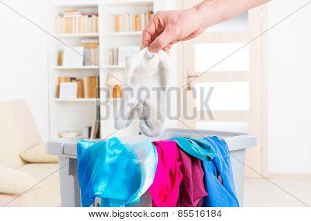 Hand holding dirty white socks over a hamper or basket
