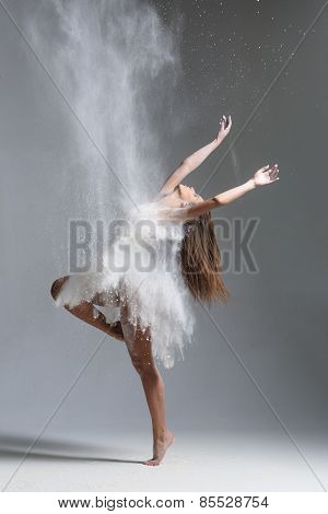 dirty in flour dancer posing on a studio background