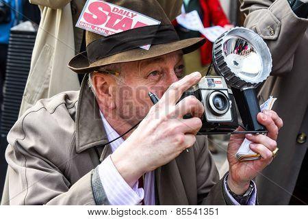 A fake paparazzi pretends to take a picture