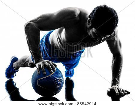 one caucasian man exercising fitness weights Medicine Ball push ups exercises in studio silhouette isolated on white background