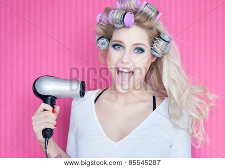 Young attractive happy laughing blonde woman with hair dryer and rollers