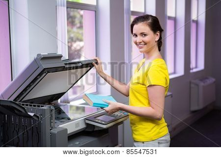 Student photocopying her book in the library at the university