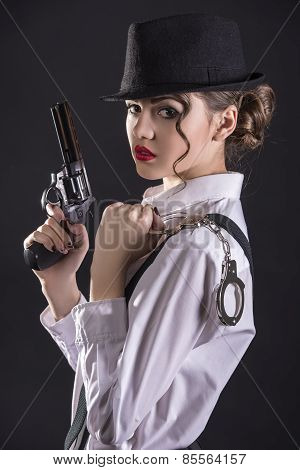 Beautiful and dangerous.Young female gangster holding the gun and holding handcuffs. isolated on dark background poster