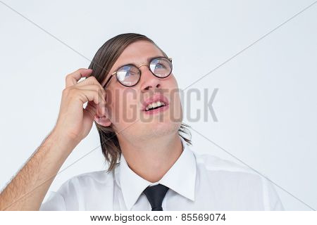 Thoughtful geeky businessman scratching his head on white background
