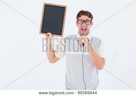 Geeky hipster holding blackboard and singing into microphone on white background