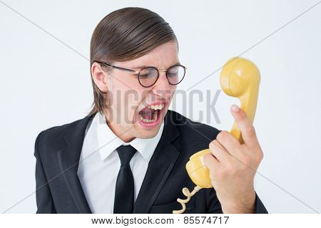 Geeky businessman shouting at retro phone on white background