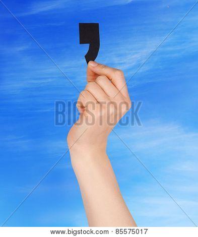 One Hand Holding Black Comma Blue Sky