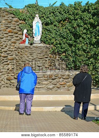 Women Prayers In Front Of A Lourdes Grotto, Catholic Shrine.