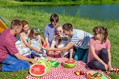 Outdoor Group Portrait Of Happy Company Having Picnic On Green Grass In Park And Enjoying Watermelon poster