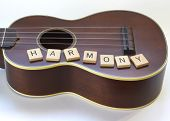 """An antique soprano Ukulele in still life with the word """"Harmony"""" spelled out in wooden, letter tiles underneath the sound hole on a white background. poster"""
