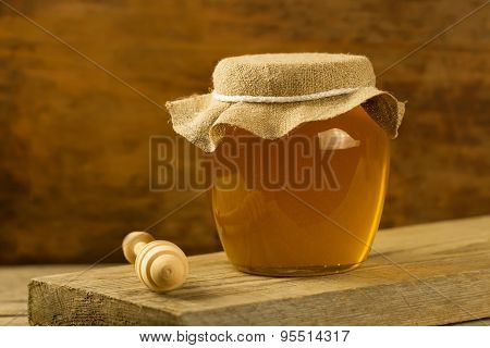 Glass Jar Of Linden Honey Withdrizzler On Wooden Background