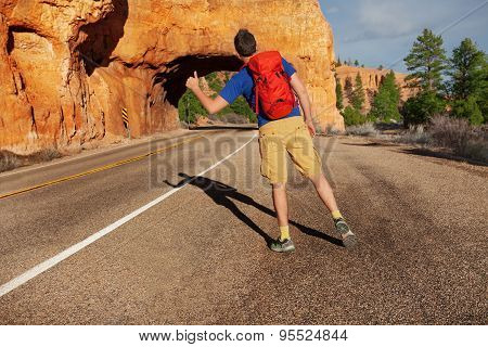 Hitch-hiking man with rucksack near Red canyon