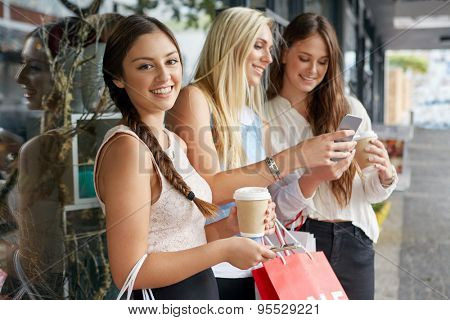 portrait of beautiful teen girl shopping in city with friends standing outdoors with mobile cell phone