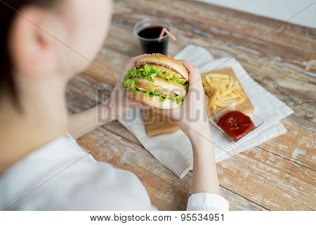 fast food, people and unhealthy eating concept - close up of woman hands holding hamburger or cheeseburger poster