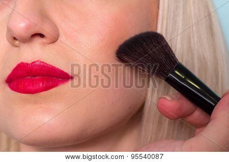 Makeup artist paints a woman blush cheekbones. Makeup.