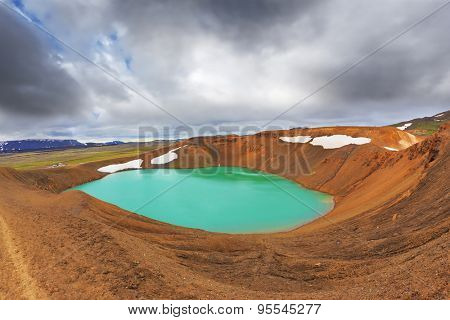 Lake water bright green color. On the shores lie snowfields from last year. Picturesque lake in the crater of an extinct volcano
