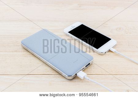 Power bank and USB cable for smartphone on wood background. poster