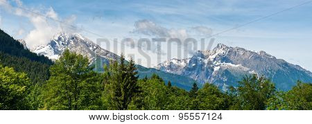 Panorama of green fir trees and snow-capped rocky mountain peaks beneath blue sky and whispy white clouds