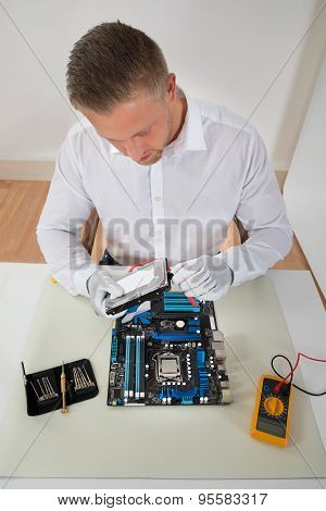 Man Connecting Harddisk With The Motherboard