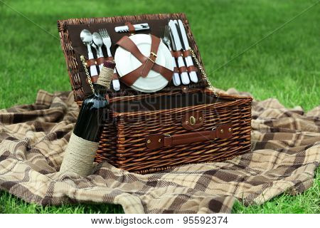 Wicker picnic basket, wine bottle and plaid on green grass, outdoors