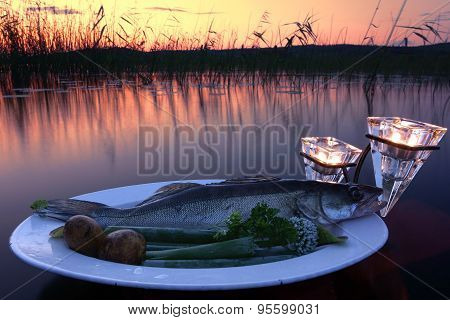 Fresh fish catch on a plate with vegetables above water by the lake at sunset time