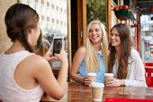 capturing memories with mobile phone camera of fun weekend teen girl friends with coffee at cafe poster