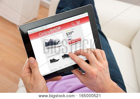 Close-up Of Man Relaxing On Couch Doing Online Shopping On Digital Tablet At Home