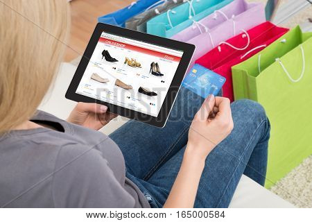 High Angle View Of Woman Shopping Online On Digital Tablet Using Credit Card At Home