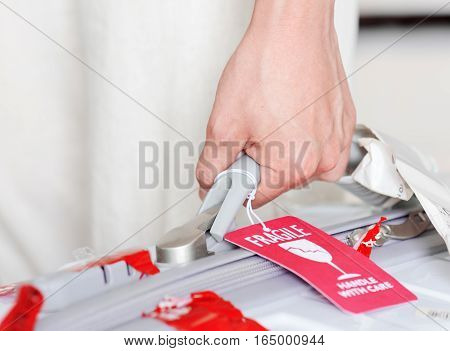 Man Holding Suitcase With Luggage Tag (fragile) At Airport