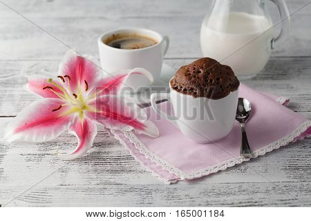 Cup cake in teacup with coffee and flower