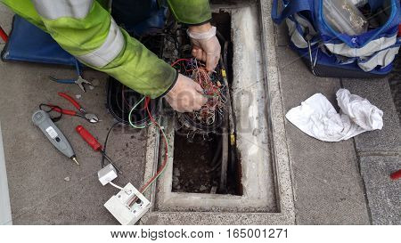 Engineer checks the phone lines on the pavement in London