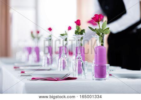 Male Waiter Placing Napkin On Wedding Table