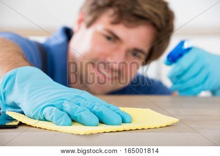 Close-up Of Worker's Hand Wearing Rubber Gloves And Cleaning Countertop