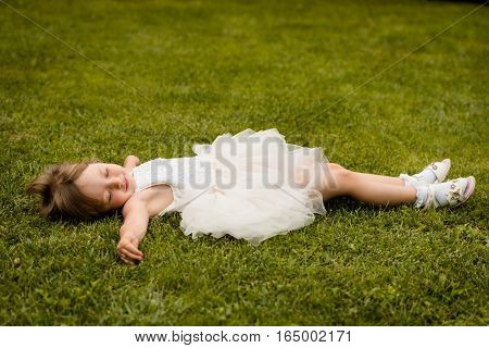 Pretty baby girl lying down on grass in the park, arms widespread.