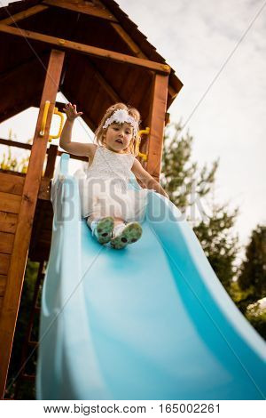 Little girl in white dress afraid as she slides down