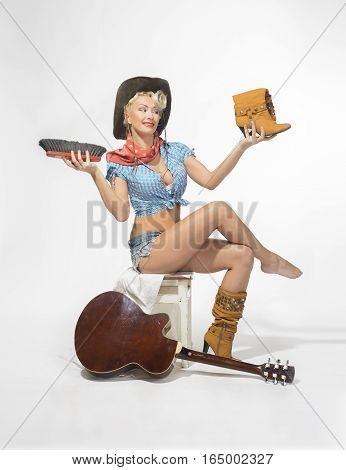 Super sexy rodeo cowgirl in torn jeans shorts and cowboy hat with a acoustic guitar brushing boots. Pin up style