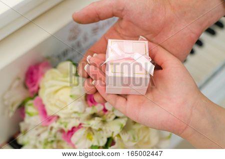 Молодожены держат в руке розовую коробочку с обручальными кольцами на фоне пианино
