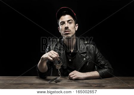Detained young man sitting at table. Studio shot.