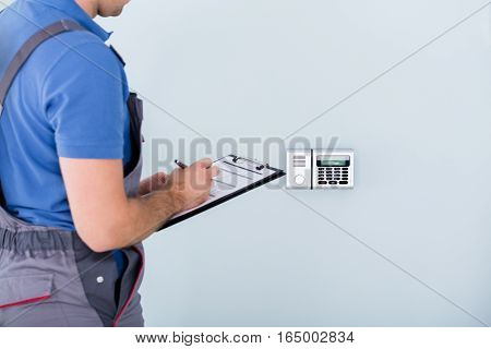 Side View Of Male Technician In Overall With Security System And Writing On Clipboard