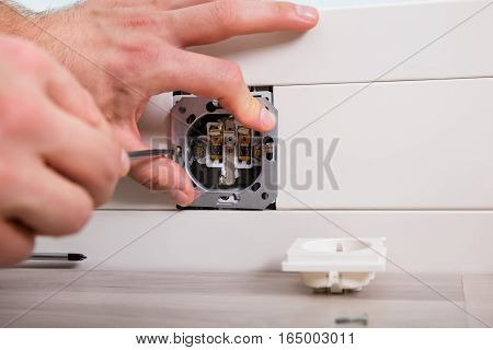 Close-up Of Man's Hand Repairing Wall Fixture Using Screwdriver