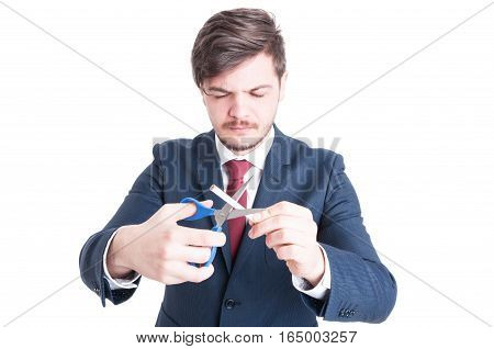 Man Wearing Suit Cutting Cigarettes With Eyes Closed