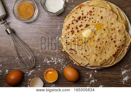 Flapjack on brown wooden table with flour, eggs and whisk