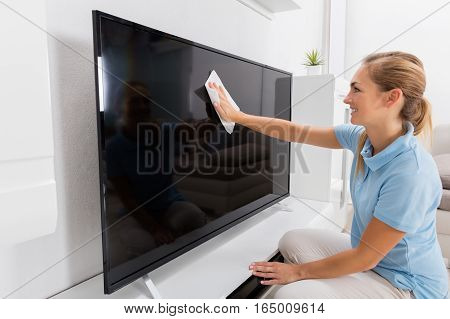 Young Smiling Woman Wiping Television Of Living Room At Home