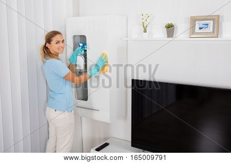 Young Smiling Woman Cleaning Furniture With Cleansing Product At Home